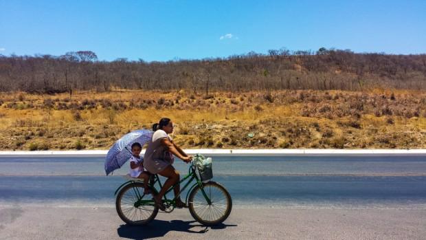Mulher anda de v=bicicleta com seu filho, na BR 365, ao fundo  vegetação de Caatinga. ( Foto Joel Silva / Folhapress)